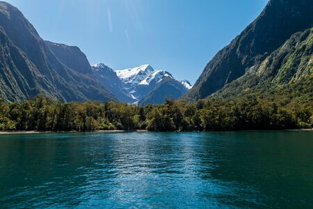Snow capped mountains with cold rainforests in the foreground are seen from a boat on the waters of Milford Sound.
