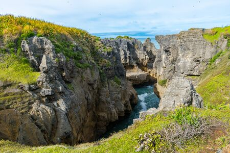 The pancake rocks on New Zealand's west coast are an interesting rock formation right next to the sea. Low coastal vegetation is followed by temperate rainforests in the distance.