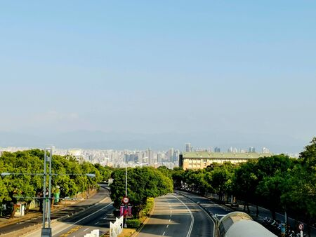 An everyday view from a pedestrian bridge in Taichung. You see the citty in the valley and mountains in the background.