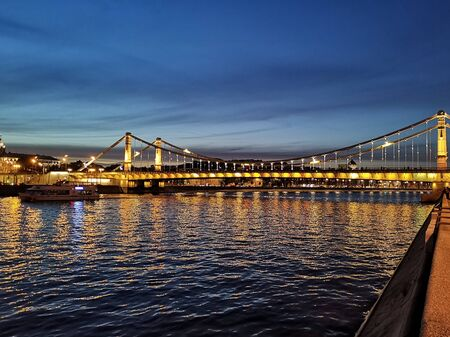 The beautiful lighted bridge over the river in Moscow by night.