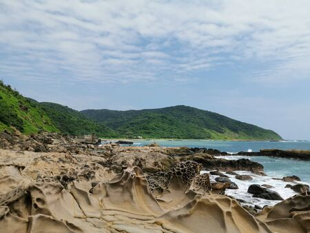 A rough stone coastline at the coast of Taiwan. Next to the coast are some tropical trees. Foto de archivo - 140648556