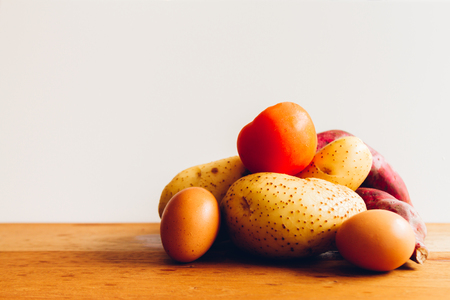 sidelight: Eggs, potatoes, tomatoes and potatoes on wooden board with white background