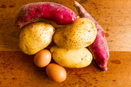 sidelight: Potatoes, sweet potatoes and eggs on wooden board