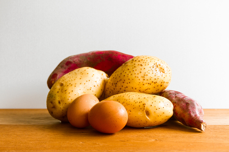 sidelight: Eggs, potatoes and sweet potatoes on wooden board with white background
