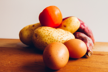 sidelight: Eggs, tomatoes, potatoes and sweet potatoes on wooden board with white background