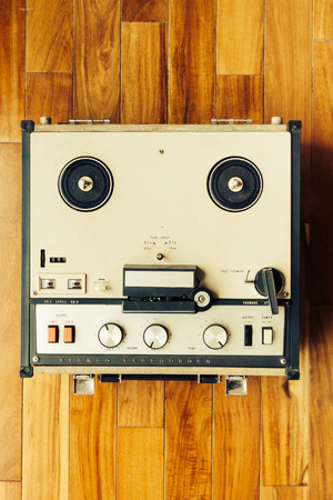 Old tape recorder over wooden floor With knobs, buttons and rolls Stock Photo