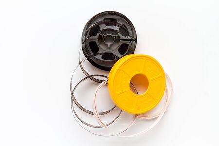 super 8: Uncoiled super 8 film reel with yellow cover on white background
