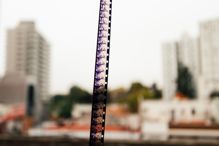 super 8: Super 8 film hanging over cityscape background