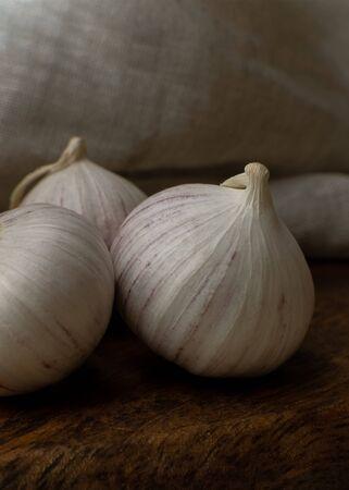 Tre aglio solo sul primo piano del fondo del tessuto della tavola di legno