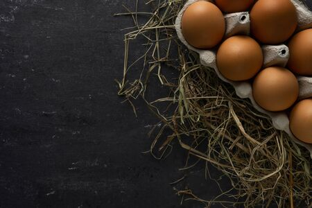 Brown chicken eggs in cardboard egg tray on hay with gray background