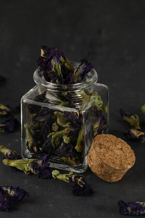 Blue tea Anchan in glass jar, cork bung, dry leaves close-up