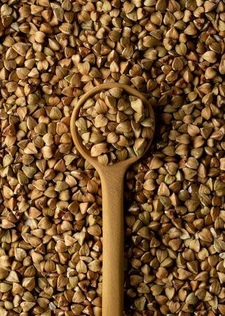 Wooden spoon with buckwheat groats on buckwheat groats texture