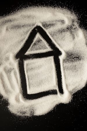 House icon drawn by sugar on a black table