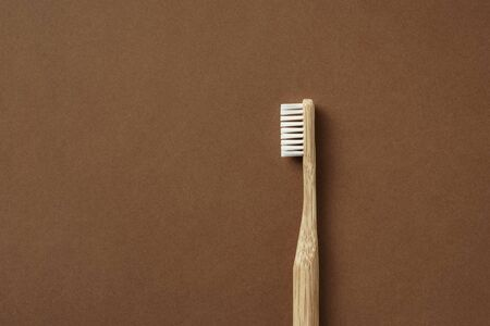 Bamboo toothbrush on brown background. Zero waste, eco lifestyle. Biodegradable material.
