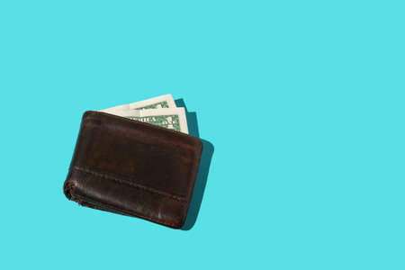 One dollar banknote in an old leather wallet