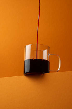 Red wine is poured in a thin stream into a glass mug over orange background. Bottom view.