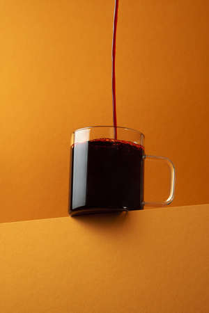 Red wine is poured into a glass mug in a thin stream over orange background. Bottom view. Modern concept design. 写真素材