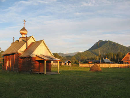 Church of Sts  Prophet Elijah in the rays of the setting sun against the backdrop of the mountains photo
