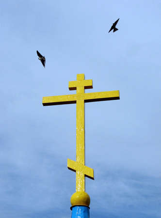 Birds fly over the cross
