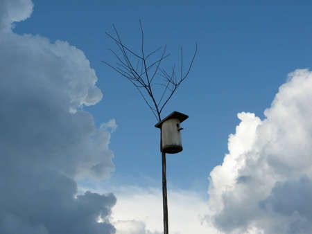 Rustic birdhouse among white clouds Stock Photo