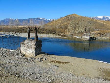 The old suspension bridge across mountain river in Gorny Altai Stock Photo