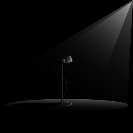 Retro microphone on dark stage with light
