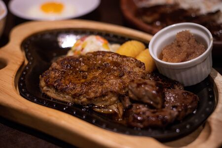 Stock Photo - Well done kobe beef steak served on the hot plate with potato