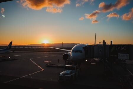 Stock Photo - Busy airport at the colorful sunrise. Preparation of the airplane before flight. Editorial
