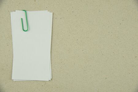 tack: white note paper with green paper clip Stock Photo