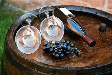 glasses and bottle of wine lying over wooden barrel photo