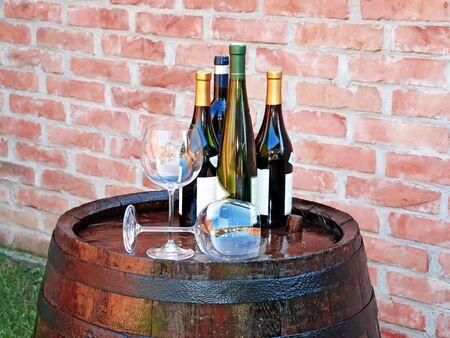 oaken: glasses and bottles of wine over wooden barrel Stock Photo