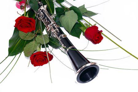 clarinete: tres rosas rojas clarinete y composici�n en blanco Foto de archivo