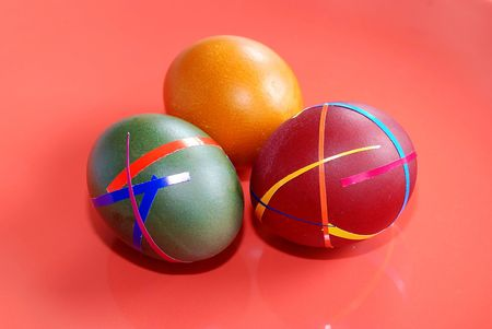 three colored ester eggs isolated over red photo
