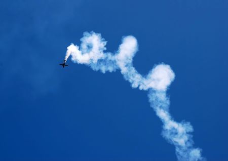 pirouette: small plane in acrobatic flight with spiral trace over blue sky Stock Photo