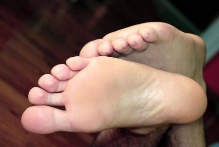 hairy legs: man feet crossed over yellow sofa on black background