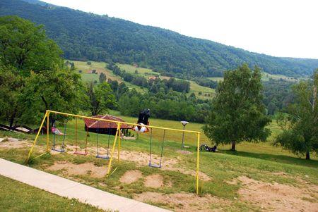 oddity: adult man swinging on swing over rural landscape
