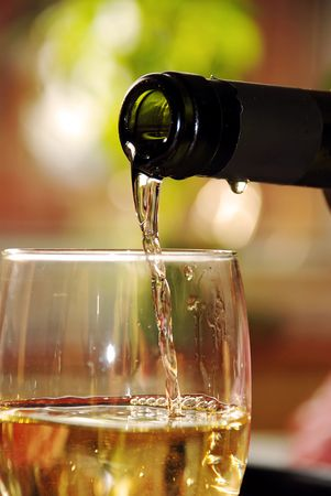 pour wine from green bottle into glass Stock Photo