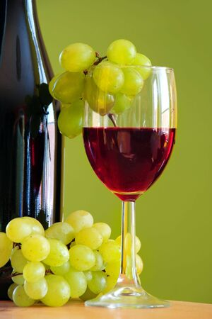 Red wine glass with grape and bottle over green Stock Photo