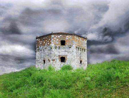 storming: Old tower of Belgrade fortress on green hill over storming sky Stock Photo