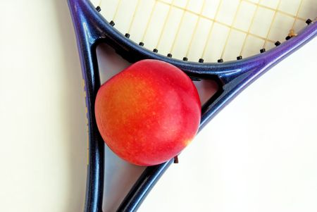 red apple in tennis racket over white isolated photo