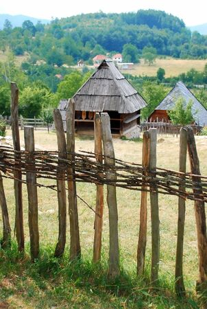 Ethnic Serbia, wooden house behind fence over rural landscape photo