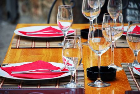 wineglasses and plates on table in restaurant photo