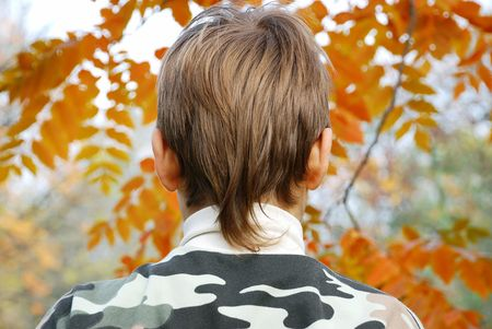 blonde minority: Boy head from back side outdoor over orange leaves Stock Photo