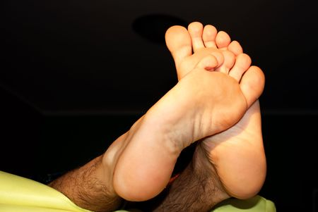 man feet crossed black background