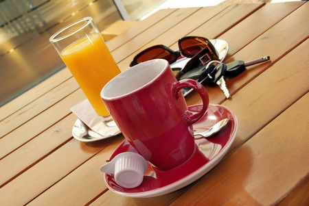 yellowish: Red cup of coffee, juice, sunglasses and car key on table Stock Photo
