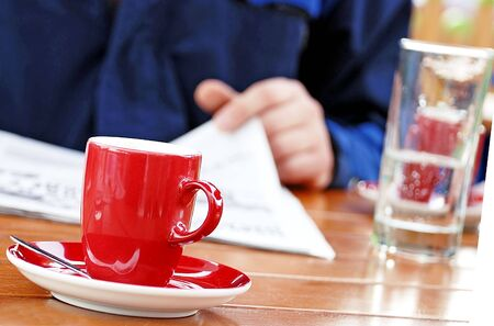 man reading newspaper drinking coffee and water photo