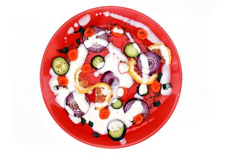 red plate with cut vegetables isolated over white photo