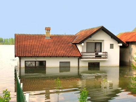 the flood tide: house with red tailed roof in river