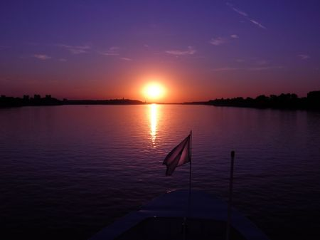 purple sunset over dark river from boat photo