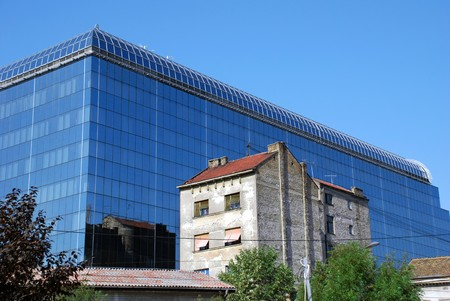 serbian: modern new glass building by old brick house in Belgrade Stock Photo